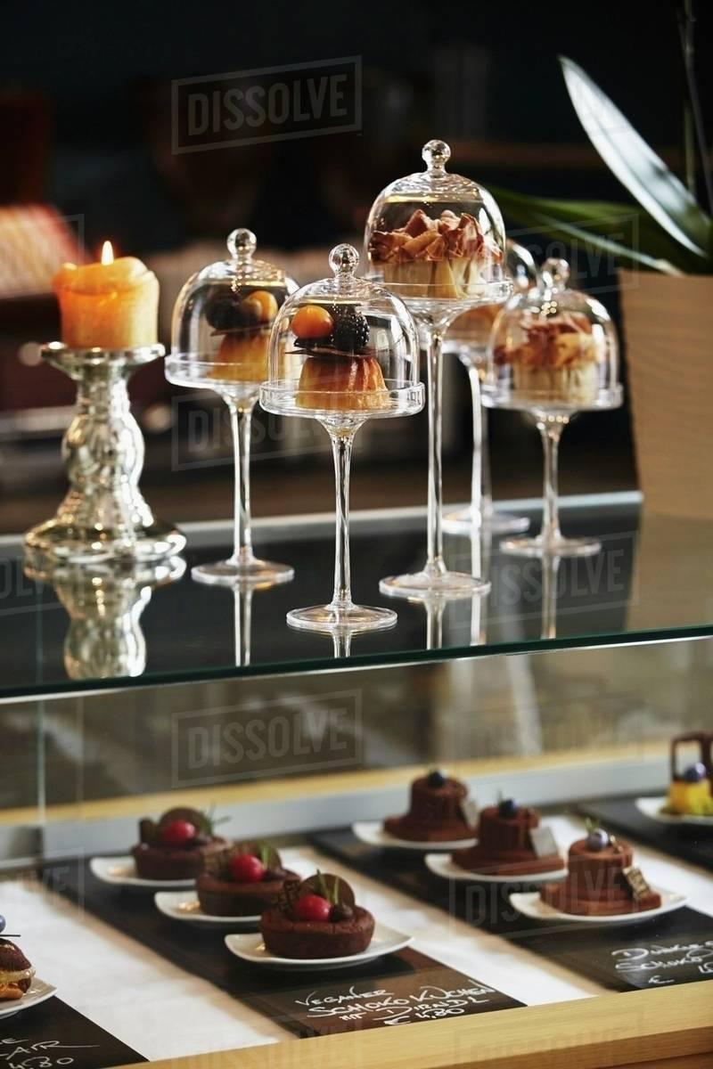 desserts under mini glass cloches on a bar in a d1062 49 672