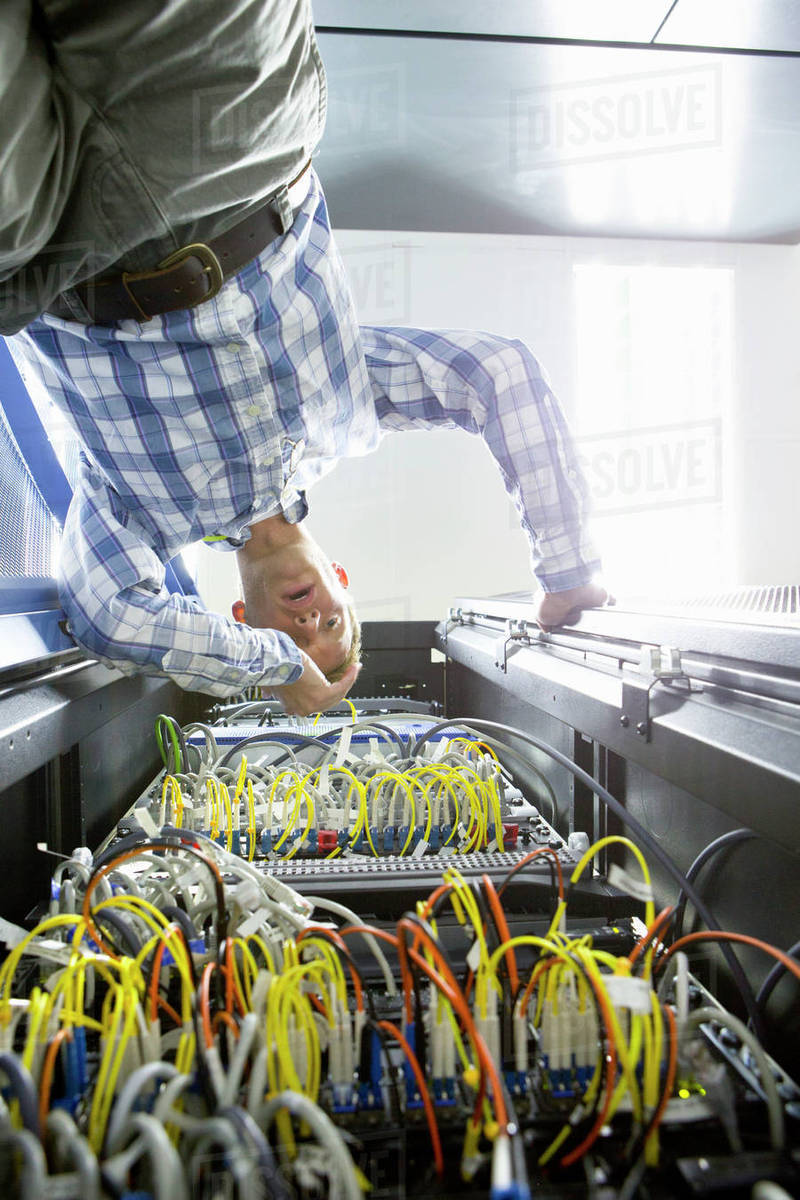 hight resolution of frustrated technician checking wiring of server in data centre