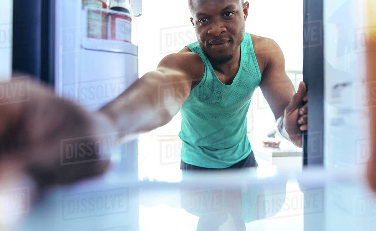 Man Placing Something In The Fridge At Home Fitness Enthusiast Using A Refrigerator After A Workout Stock Photo Dissolve