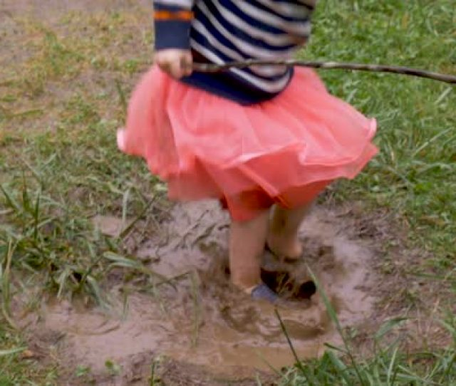 Overhead Of A Young Girl Splashing Around In A Mud Puddle In A Skirt In Slow