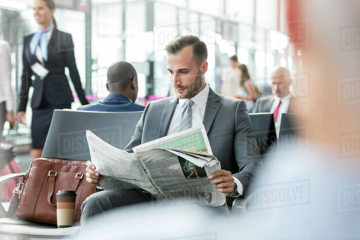 Businessman Reading Newspaper In Airport Departure Area