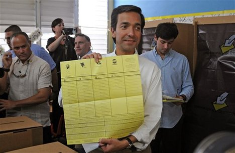 """In this image released by the New Progressive Party, Puerto Rico's Gov. Luis Fortuno shows his ballot to the press as he votes at a polling station in Guaynabo, Puerto Rico, Tuesday, Nov. 6, 2012. Puerto Ricans are electing a governor as the U.S. island territory does not get a vote in the U.S. presidential election. But they are also casting ballots in a referendum that asks voters if they want to change the relationship to the United States. A second question gives voters three alternatives: become the 51st U.S. state, independence, or """"sovereign free association,"""" a designation that would give more autonomy."""