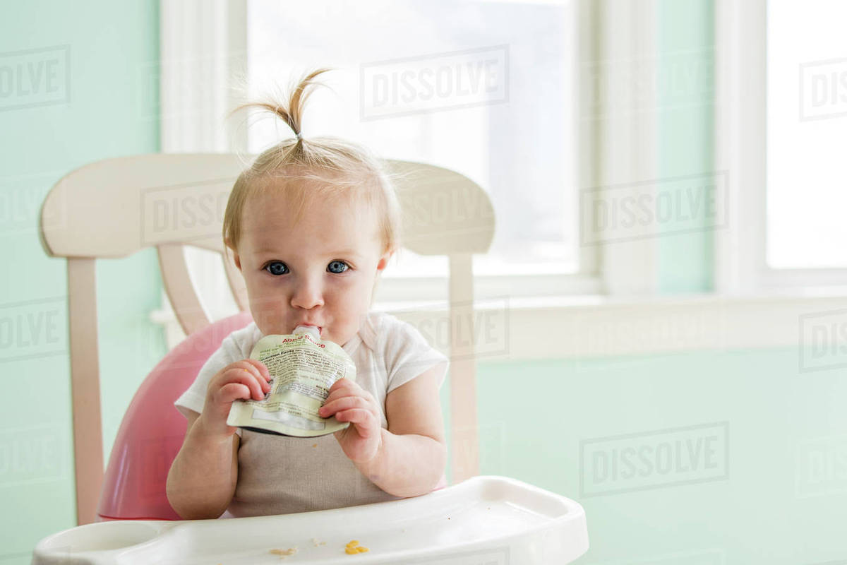 baby girl chair wheelchair stairs portrait of cute eating apple sauce from pack while sitting on high at home