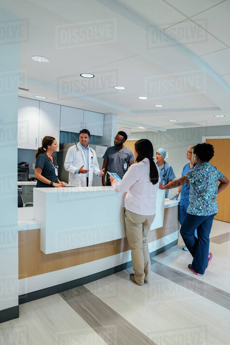 Doctors discussing during meeting at hospital reception