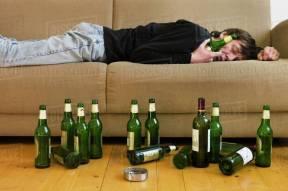Germany, Hessen, Frankfurt, Drunk man lying on sofa with empty beer bottles  - Stock Photo - Dissolve