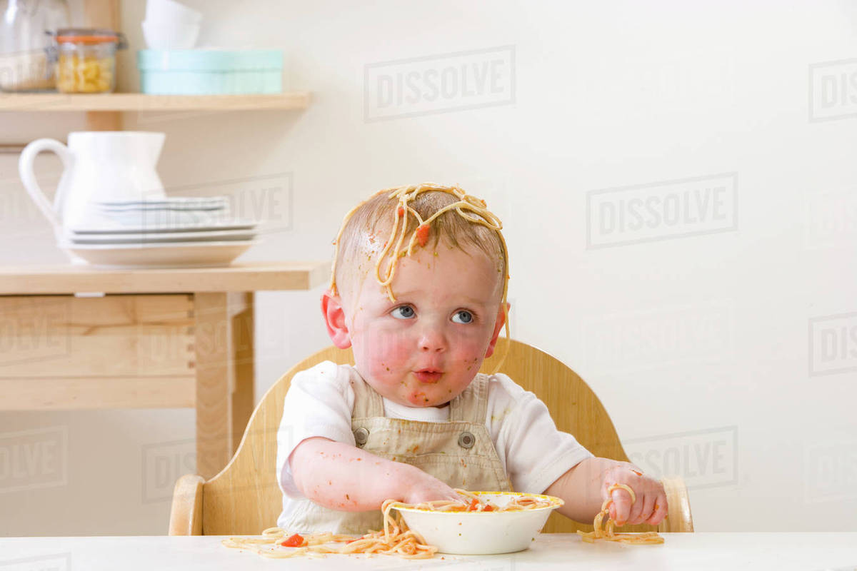 Toddler Boy Chair Messy Baby Boy In High Chair Eating Spaghetti Stock