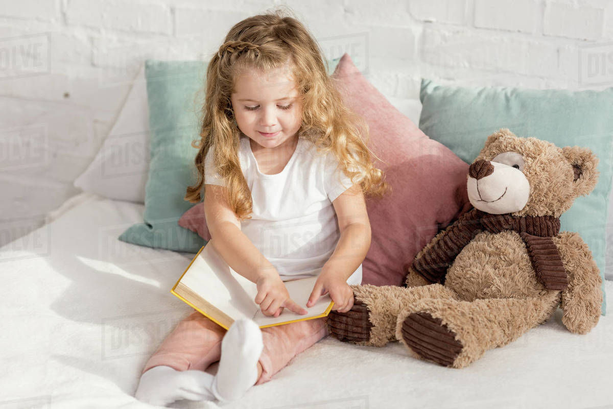 Adorable Cheerful Kid Playing With Teddy Bear And Reading