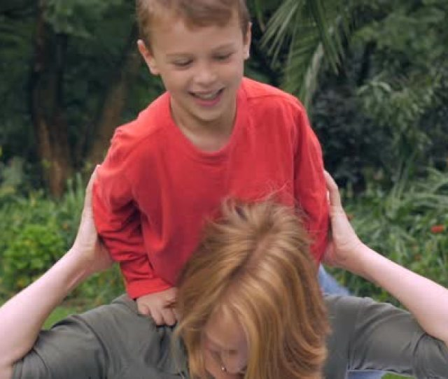 A Red Headed Mother Plays With Her Adorable Young Blond Haired Son On Her Shoulders While