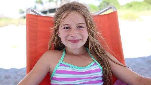 9yearold girl sitting in a beach chair  Stock Video