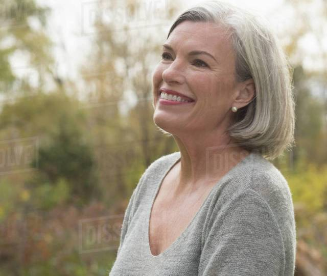 Happy Mature Woman Looking Away While Standing At Park During Autumn