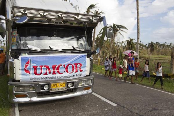 Community members walk past a food distribution site for the United Methodist Committee on Relief following Typhoon Haiyan in Dagami, Philippines, in 2013. Photo by Mike DuBose, UMNS.