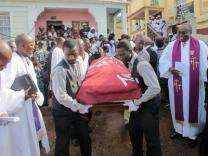 "The body of 107-year-old Rev. Isaac Momoh Ndanema is led out of church for burial. Often called ""Pa Ndanema,"" he chose to live simply and served as a peacemaker and social evangelist while encouraging the local language.Phileas Jusu, United Methodist Communications."
