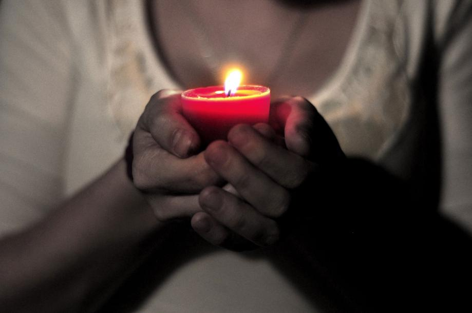 Praying while holding a candle.