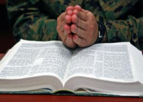Hands in prayer over a Bible.