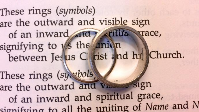 Rings sit on text from the wedding service in the United Methodist Book of Worship. Photo illustration by Fran Walsh, United Methodist Communications.