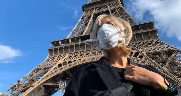 Une femme masquée au pied de la Tour Eiffel