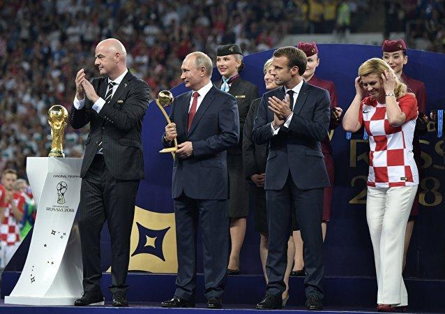 15 июля 2018. Президент ФИФА Джанни Инфантино, президент РФ Владимир Путин, президент Франции Эммануэль Макрон и президент Хорватии Колинда Грабар-Китарович (слева направо) на церемонии награждения победителей чемпионата мира по футболу FIFA 2018 года на стадионе Лужники.