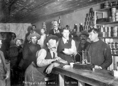 In a Dawson City grocery store, a prospector pays for his items with a bag of gold dust.