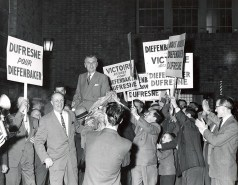 "John Diefenbaker smiles as he is carried on the shoulders of members of a large crowd in Quebec City bearing election posters with slogans such as ""Victoire assure pour Diefenbaker Dufresne."" Diefenbaker was re-elected with the largest majority to date in Canadian history, defeating Pearson's Liberals."