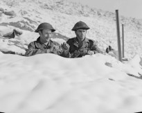 Two Canadian Soldiers in Snow During Korean War. They are hiding behind a snowbank.