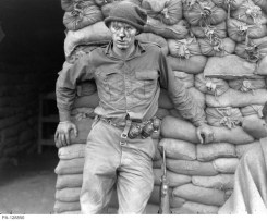 An Injured Canadian Soldier with blood on his face waits for medical aid. He's leaning against the barracks.