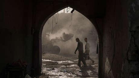 Dos trabajadores de la construcción llevan un generador mientras una excavadora elimina escombros de las tiendas destruidas en la Ciudad Vieja de Mosul, Irak.