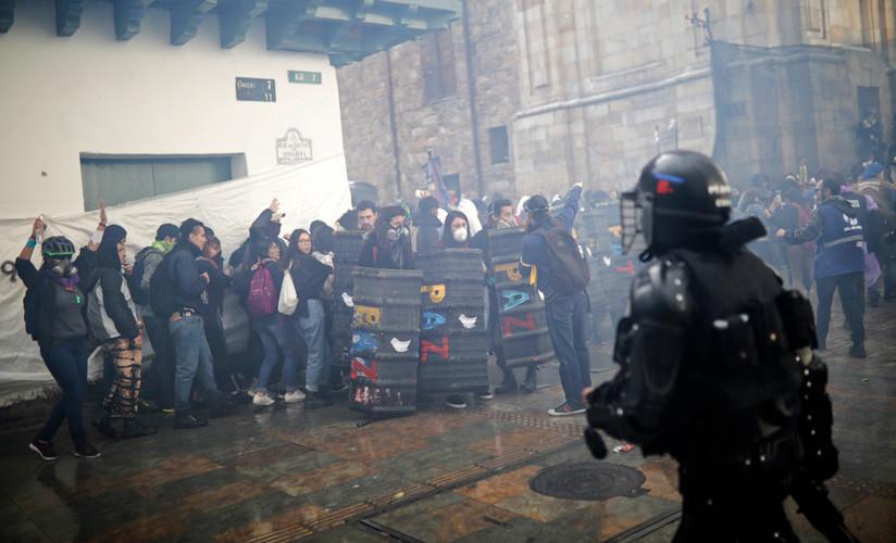 """Los manifestantes con escudos que dicen """"paz"""" en medio de gases lacrimógenos lanzados por la Policía Nacional en Bogotá, Colombia, el jueves 10 de octubre de 2019."""