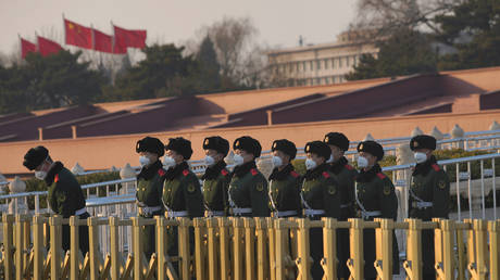 Paramilitary officers wearing masks line up in front of the Tiananmen Gate, as the country is hit by an epidemic of the new coronavirus, in Beijing, China January 30, 2020. © REUTERS/Stringer