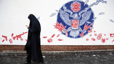 FILE PHOTO. A woman walks past an anti-US mural on the former U.S. Embassy's wall in Tehran, Iran.