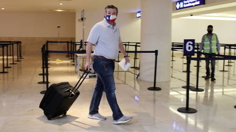 Republican Senator Ted Cruz (Texas) carries his luggage at the Cancun International Airport before boarding his plane back to the US, in Cancun, Mexico February 18, 2021.
