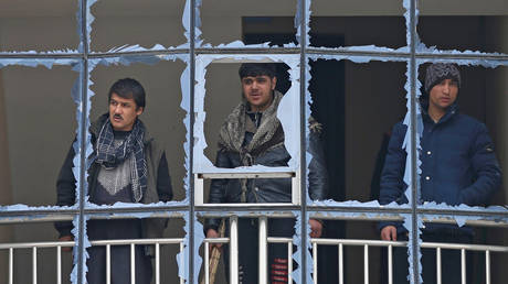 File photo: Men peer through windows of their building blown out by a bomb in Kabul, Afghanistan, December 20, 2020.