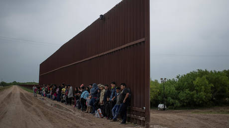 FILE PHOTO: Asylum-seeking migrants from Central America line-up along the border wall as they wait to surrender to the US border patrol, in Penitas, Texas, April 2, 2019.