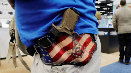 A man carries his Glock handgun in a custom holster during the National Rifle Association (NRA) annual meeting in Indianapolis, Indiana, April 27, 2019.