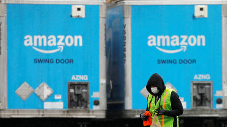 FILE PHOTO: A worker walks by trucks parked at an Amazon facility in Long Island, New York.