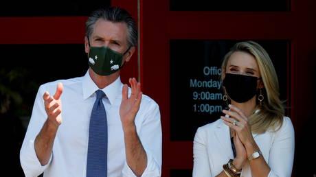 California Governor Gavin Newsom and wife Jennifer Siebel Newsom applaud Kamala Harris in San Leandro, California
