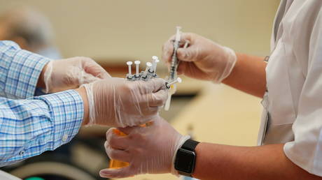 FILE PHOTO: Walgreens workers exchange doses of coronavirus vaccines at an immunization site in Evanston, Illinois.