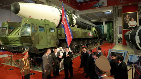 North Korea's leader Kim Jong-un speaks to officials next to weapons and vehicles on display, including long-range missiles, at an arms expo in Pyongyang, North Korea, October 12, 2021.