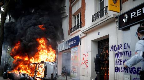 Un véhicule en feu devant la concession Renault attaquée à Paris, le 1er mai