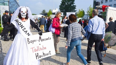Protestataire portant une robe de mariée sur laquelle est écrit «Bayer+Monsanto= mariage létal», lors d'une manifestation contre le rachat par Bayer de Monsanto, à l'extétieur d'un centre de conférence à Bonn où se tient le rendez-vous annuel de Bayer.