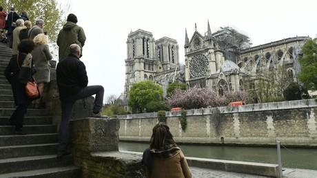 Les passants contemplent les ruines depuis les quais de la Seine le 16 avril au matin.