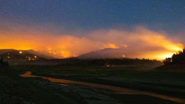 In this long exposure photograph, flames surround a drought-stricken Shasta Lake during the