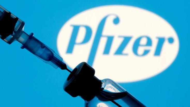 FILE PHOTO: A vial and syringe are seen in front of a Pfizer logo in this illustration taken on January 11, 2021.