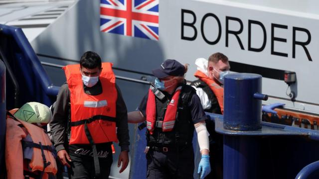 A British Border Force staff member leads a migrant into Dover harbour, in Dover, Britain, June 6, 2021.