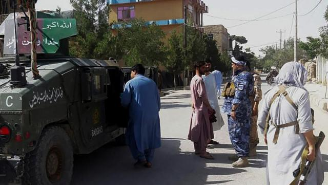 Afghan security personnel stand guard along a road amid ongoing fight between government forces and Taliban in western city of Qala-e- Naw, capital of Badghis province, on July 7, 2021.