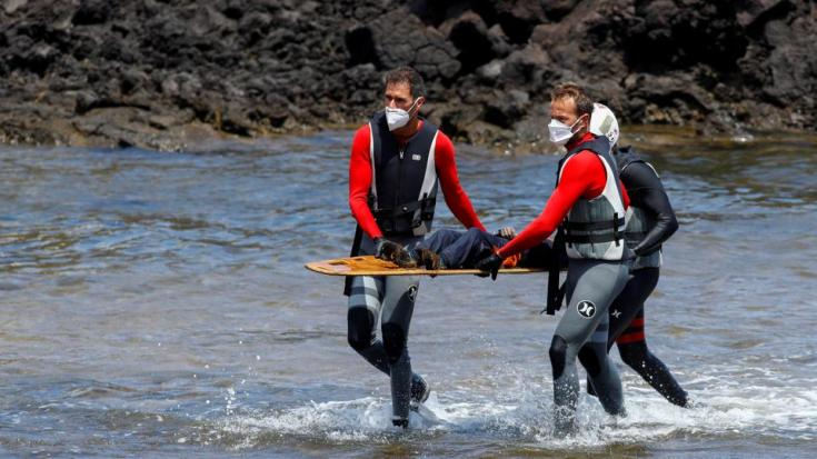 Rescue workers carry the body of a dead person after a boat with 46 migrants from the Maghreb region capsized in the beach of Orzola, in the Canary Island of Lanzarote, Spain June 18, 2021.