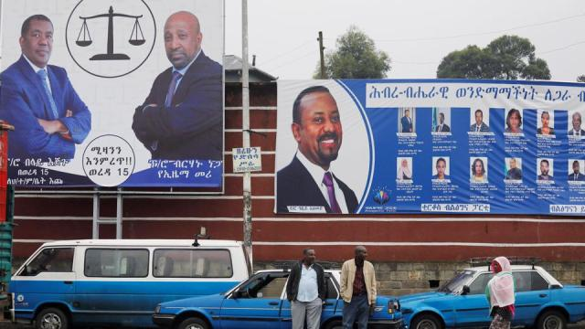 Taxi drivers stand in front of campaign banners of the Ethiopian PM Abiy Ahmed, and Birhanu Nega, head of the Ethiopian Citizens for Social Justice party, hours before elections, in Addis Ababa on June 20, 2021.