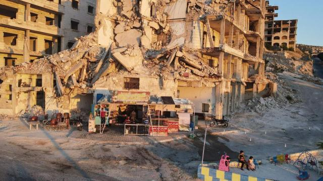 Children gather in the playground in front of Abu Ali's cafe, set up on the ground floor of a building heavily damaged during the civil war, in the Jabal al-Arbain hiltop residential area, in the Syrian town of Ariha in the rebel-held northwestern Syrian Idlib province, on July 11, 2021.