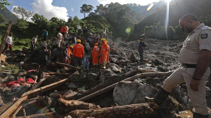 Members of National Disaster Response Force (NDRF) inspect the site of a landslide after heavy rains at Boh village in Kangra district of India's Himachal Pradesh state on July 13, 2021.