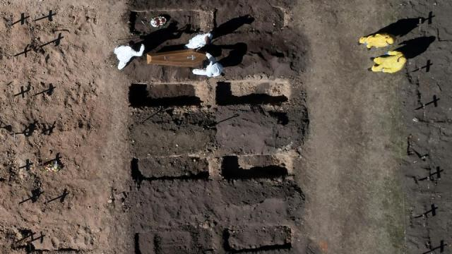 In this file photo taken on August 11, 2020, aerial view of workers burying a coffin in an area cleared to accommodate new graves to cope with demand during the coronavirus pandemic in the Chacarita cemetery in Buenos Aires.