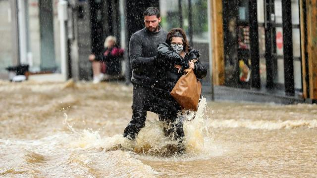 A man helps a women walk along a flooded street in Spa, as bad weather conditions floods in the city centre on July 14, 2021.